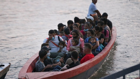 Honduran migrant families trying to reach the U.S. cross the Usumacinta river on a boat, as seen from La Tecnica in Lacandon…