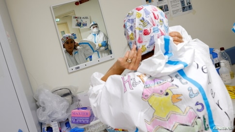A medical worker wearing protective equipment (PPE) decorated with Easter themed drawings gets ready before starting her shift…