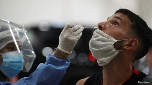 A healthcare worker takes a swab sample from a man to be tested for the coronavirus disease (COVID-19), in Buenos Aires,…