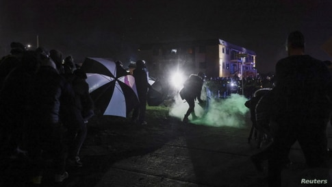 A protester attempts to contain fumes from a chemical irritant released by the police outside an apartment complex near the…