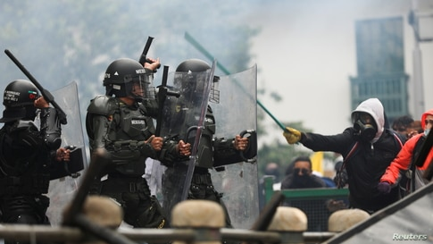 Demonstrators clash with members of security forces during a protest against the tax reform of President Ivan Duque's…