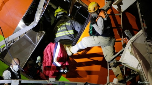Rescuers work at a site where an overpass for a metro partially collapsed with train cars on it at Olivos station in Mexico…