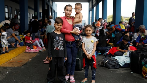 Venezuelan migrant Genesis Valera, 27, who is six months pregnant, poses for a picture with her children Sebastian, 7, Claudia,…