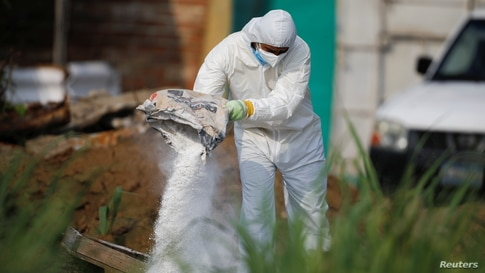 A forensic expert throws lime on discarded protective equipment used where authorities are excavating a clandestine cemetery…