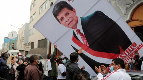 Supporters of Peru's presidential candidate Pedro Castillo handle a large placard of Castillo the day after a run-off election,…