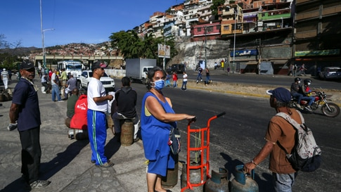 A woman waiting to buy a propane gas canister wears a face mask as a preventive measure against the spread of the new…