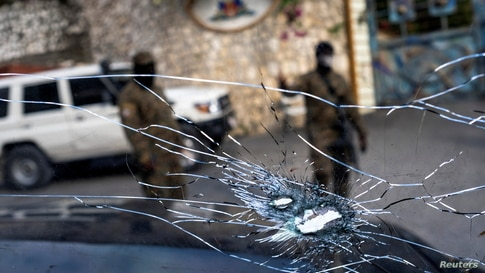 Bullet holes in the window of a presidential security car are seen in the parking lot of the residence of late President…