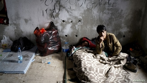 FILE PHOTO: Afghan refugees rest in an old abandoned beach house as they wait to board a dinghy sailing off for the Greek…