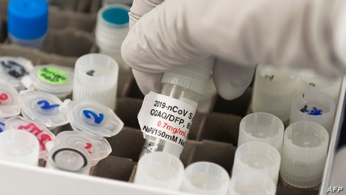 (FILES) In this file photo Dr. Nita Patel, Director of Antibody discovery and Vaccine development, lifts a vial with a…