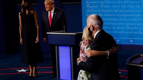 US First Lady Melania Trump (L) stands with US President Donald Trump as Jill Biden (R) hugs husband Democratic Presidential…