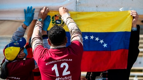 "Venezuelan migrants hang a Venezuelan National flag during a ""popular consultation"" called by Venezuelan opposition leader Juan…"