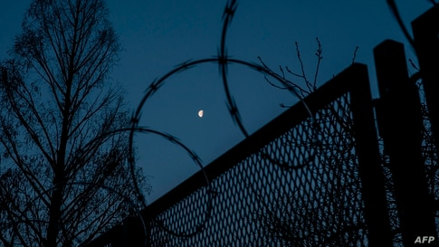 WASHINGTON, DC - MARCH 04: The moon is seen between the barbed wire fencing that surrounds the U.S. Capitol before sunrise on…