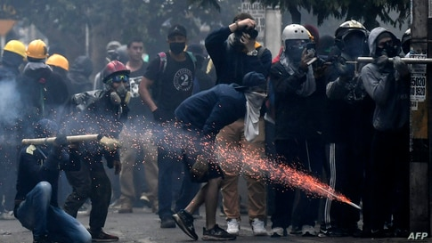 TOPSHOT - Demonstrators clash with riot police in a new protest against the government of Colombian President Ivan Duque in…