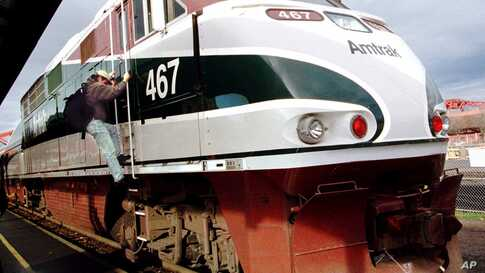 FILE - In this Nov. 30, 1998 file photo, engineer David Estes climbs down from the engine of an Amtrak train after arriving at…