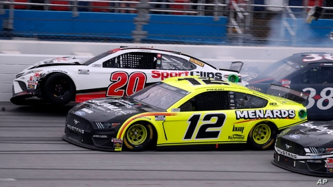 Winner Ryan Blaney (12) approaches the finish line as driver Erik Jones (20) crashes at the finish of a NASCAR Cup Series auto…