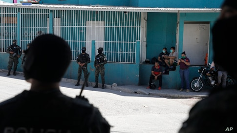 Residents with protective masks watch from their stoop as soldiers and police cordon off the Lincoln neighborhood to prevent…