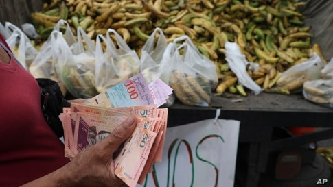 In this May 8, 2019 photo, a woman counts 5,000 Bolivars, almost one dollar, to buy a bag of bananas in the Petare area of…