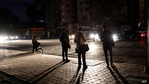 People wait for a public transportation on a street during a blackout in Caracas, Venezuela, Monday, July 22, 2019. The lights…
