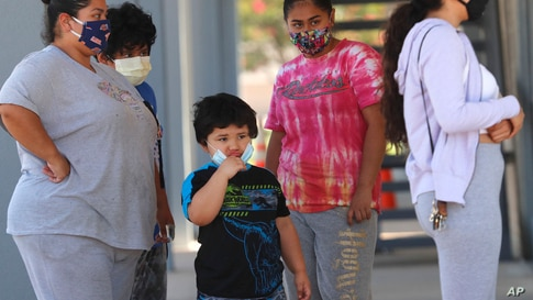 A family waits in line to check in for free COVID-19 tests at a Parkland Hospital mobile walk-up testing site in the Red Bird…