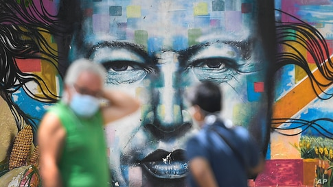 Pedestrians wearing masks to curb the spread of the new coronavirus chat in front of a mural of late President Hugo Chavez, in…