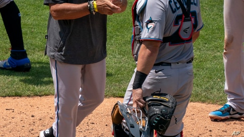 Miami Marlins manager Don Mattingly, left, changes pitchers as catcher Francisco Cervelli, right, looks on during the fourth…