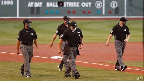 Umpires, wearing protective masks due to the COVID-19 virus outbreak, walk to home plate prior to a baseball game, Monday, July…