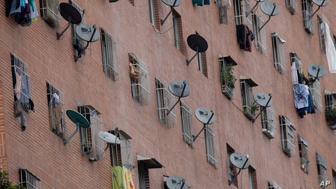 DirectTV satellite dishes dot the facade of the Great Mission public housing project in Caracas,Venezuela, Friday, May 22, 2020…