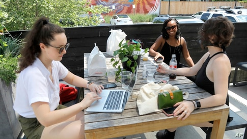 Natalie Boegel, left, Shianne Williams-Brwon and Caitlin McAfee talk while eating from a restaurant at the R. House food hall,…