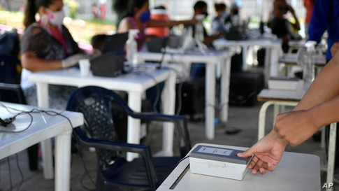 A woman places her thumb on a fingerprint scanner at a validation center to certify the authenticity of voter data in Caracas,…