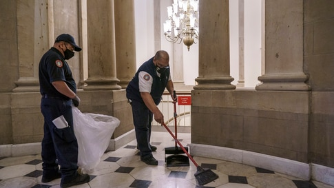 Workmen clean up debris outside the office of Speaker of the House Nancy Pelosi on the day after violent protesters loyal to…