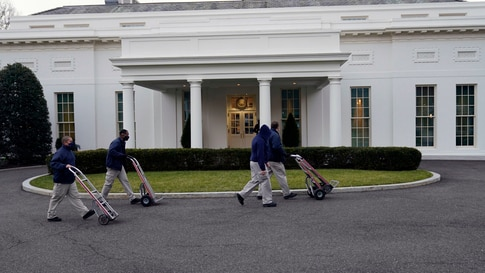 Workers walk with hand trucks past the West Wing of the White House, as offices in the White House complex are being packed up…