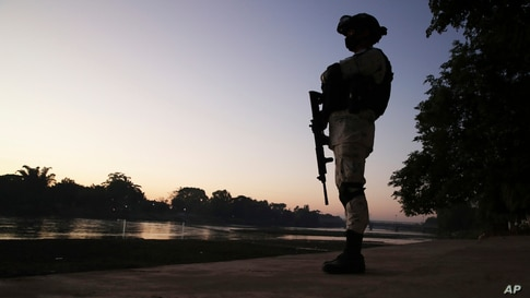 A Mexican National Guard stands on the bank of the Suchiate River, the natural border with Guatemala near Ciudad Hidalgo,…