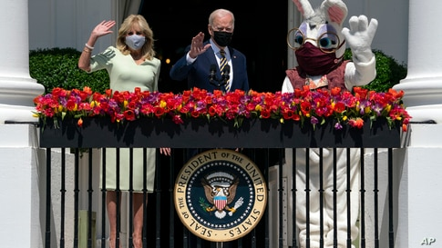 President Joe Biden and first lady Jill Biden wave from the Blue Room Balcony as they participate in an Easter event at the…