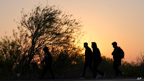 Migrants walk near a gate on the U.S.-Mexico border wall after they were spotted by a U.S. Customs and Border Protection agent…