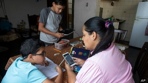 Leidy Martinez reads her son's homework assignment on her cell phone, as her other son Joandry, 12, checks the internet…