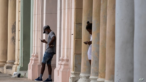 People use their cell phones where a pre-paid public wifi connection is working near the Malecon seawall in Havana, Cuba,…
