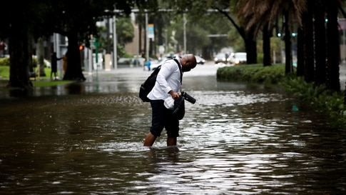 A man walks in floodwaters caused by Tropical Storm Eta in a street at Brickell neighborhood in Miami