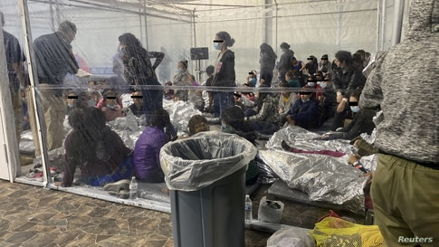 Migrants crowd a room with walls of plastic sheeting at the U.S. Customs and Border Protection temporary processing center in Donna