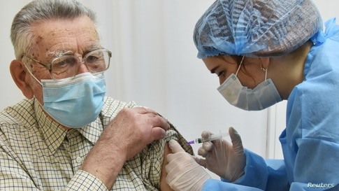 An elderly man receives the COVID-19 vaccine in Lviv