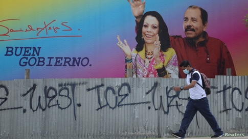 Man walks by billboard showing Nicaragua's President Ortega and Vice President Murillo in Managua