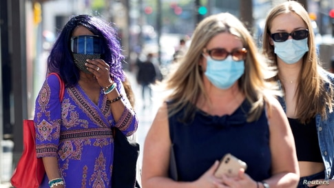 FILE PHOTO: People wearing face protective masks walk on Hollywood Blvd during the outbreak of the coronavirus disease (COVID-19), in Los Angeles