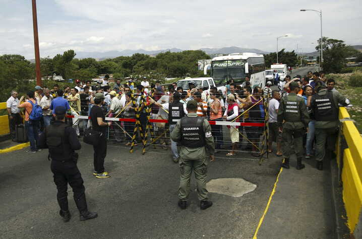 People wait in front of Venezuelan soldiers to try to cross the Simon Bolivar international bridge on the border with Colombia at San Antonio in Tachira state, Venezuela August 22, 2015. Venezuela's closure of two border crossings with Colombia hurts