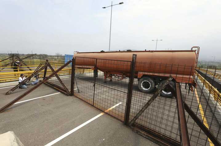 Journalists record a fuel tanker, cargo trailers and makeshift fencing, used as barricades by Venezuelan authorities attempting to block humanitarian aid entering from Colombia on the Tienditas International Bridge that links the two countries as see