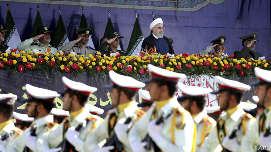 Iran's President Hassan Rouhani, top center, reviews army troops marching during the 38th anniversary of Iraq's 1980 invasion of Iran, in front of the shrine of the late revolutionary founder, Ayatollah Khomeini, outside Tehran, Iran, Sept. 22, 2018.