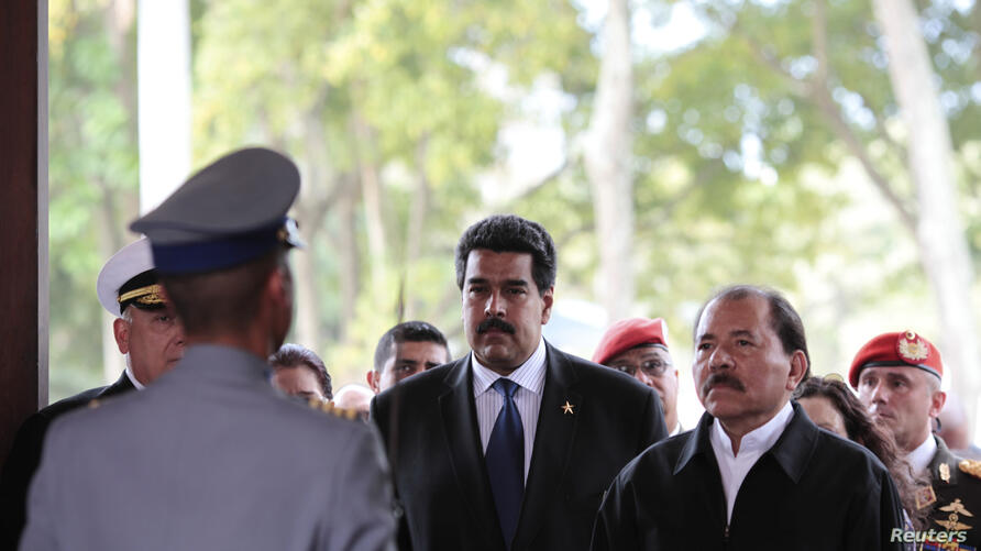 Nicaragua's President Daniel Ortega (R) stands next to Venezuela's Vice-President Nicolas Maduro (C) as they visit the wake of late Venezuelan President Hugo Chavez, which is lying in state, at the military academy in Caracas March 9, 2013, in this pictur