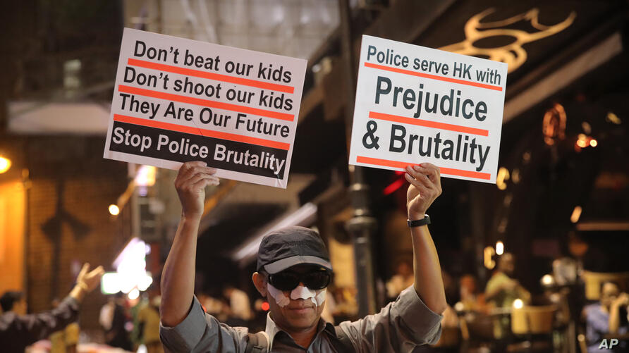 A man holds signs decrying police brutality in Hong Kong, Oct. 31, 2019.