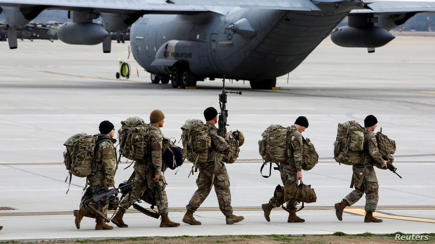 Paratroopers from the U.S. Army's 82nd Airborne Division walk out to a waiting transport plane bound for Colombia to…