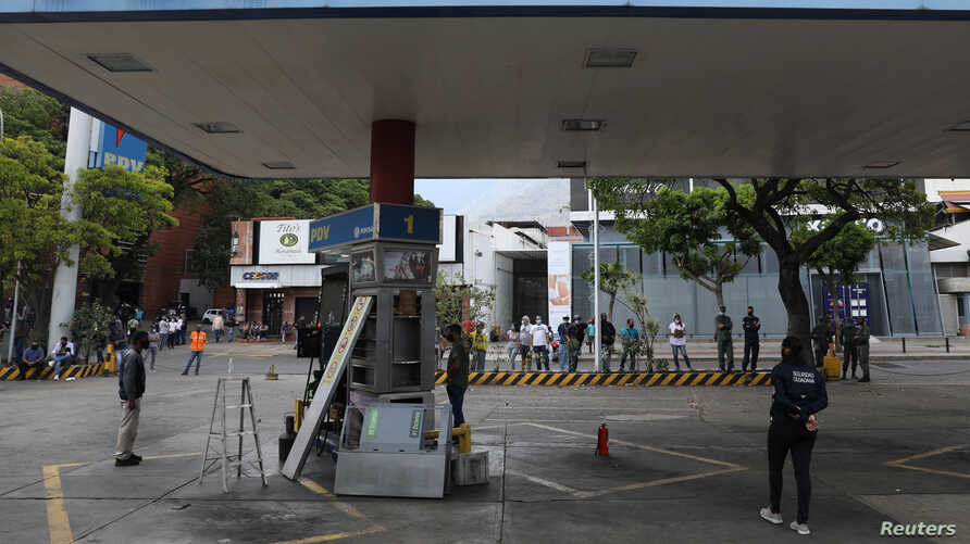 Customers wait while a fuel dispenser machine is fixed at a gas station in Caracas, Venezuela April 23, 2020. Picture taken…
