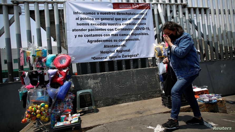 A woman walks past a banner placed at the fence of a hospital announcing that is at full capacity amid the coronavirus disease …