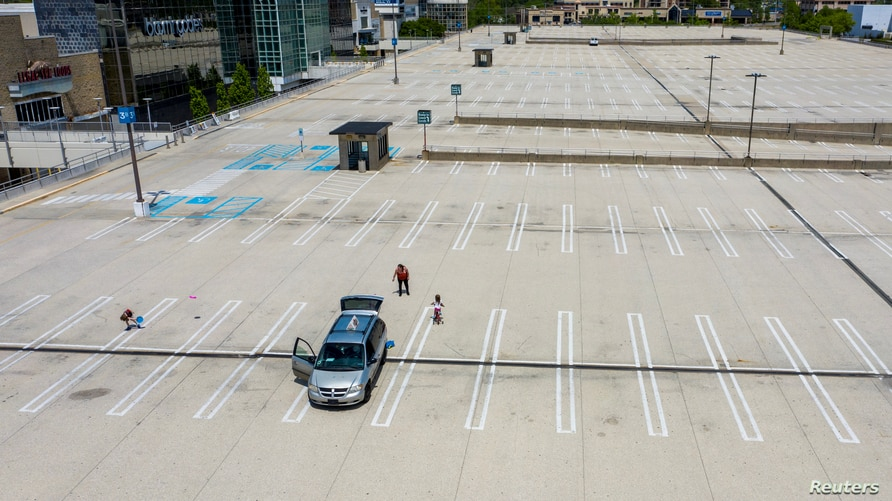 A family plays frisbee in an empty parking lot next to the King of Prussia Mall which remains closed due to the ongoing…